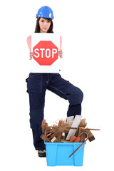 girl with safety helmet holding stop sign