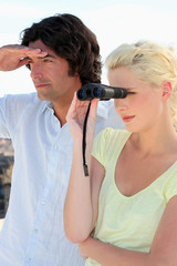 Couple looking through binoculars whilst on vacation