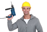 A construction worker holding a drill.