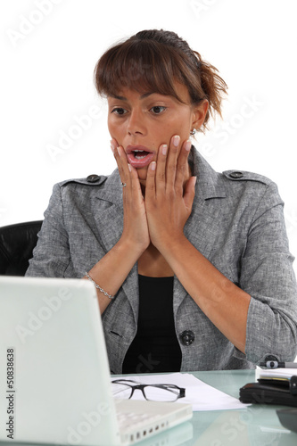 Shocked woman looking at computer screen