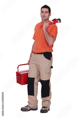 Handyman stood with wrench and tool kit
