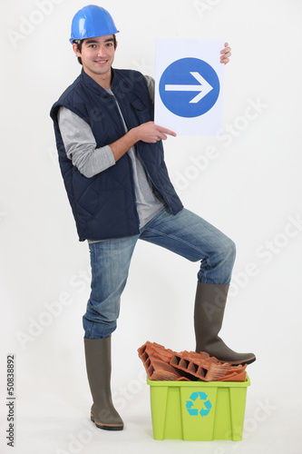 young bricklayer in studio holding sign with arrow