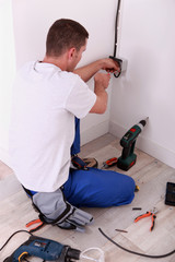 electrician screwing an electrical outlet