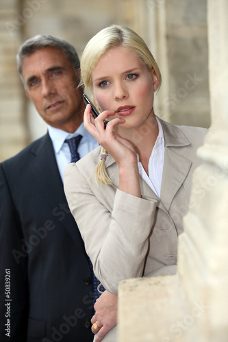 Woman with a cellphone and her older partner