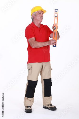 Middle-aged manual worker holding spirit-level