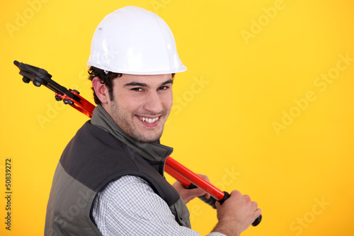 Man resting large bolt cutters over shoulder