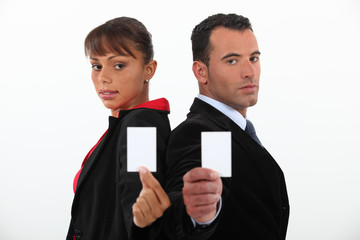 Businessman and woman holding calling cards