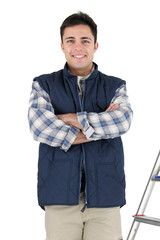 craftsman standing cross-armed in studio with ladder and tools