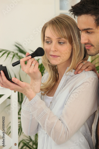 Woman applying blusher whilst boyfriend watches