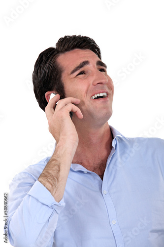 A businessman laughing over the phone.