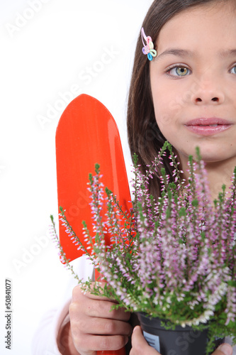 little girl with shy smile gardening