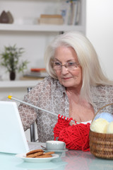 Elderly lady knitting by laptop