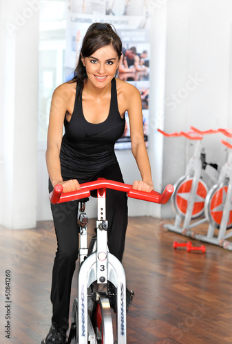 canvas print picture Junge Frau auf Spinningrad