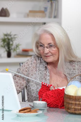 Elderly lady knitting by laptop