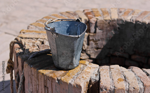 A water well with an old bucket - 50841823