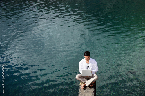 Businessman sat by lake