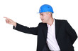 Businessman in a hardhat pointing at something