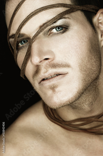 Portrait of a beautiful young man with strip of leather