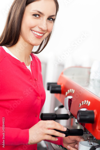 Female barista by coffee maker