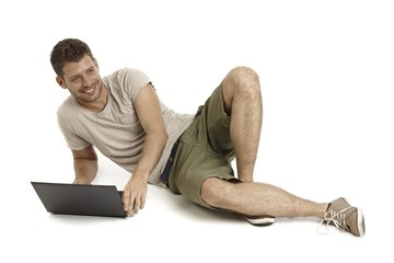 Young man using laptop computer smiling