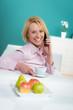 frau trinkt tee beim telefonieren