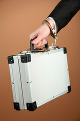 Hand with handcuff and suitcase, on color background