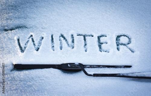 Winter written in snow on car windscreen below windscreen wiper - 50854657