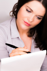 Young professional female writing on pad