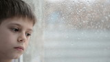 Boy looks at rain in a window