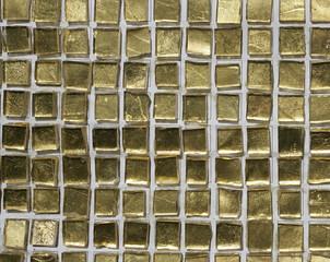 Goldene Mosaiksteinchen, angeordnet auf einer Wand