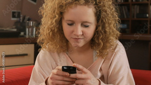 Young girl sitting on a couch and texting