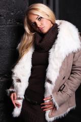 Beautiful blond woman in a fur near bricks wall
