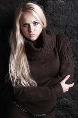 beautiful blond woman in brown sweater. Black bricks background