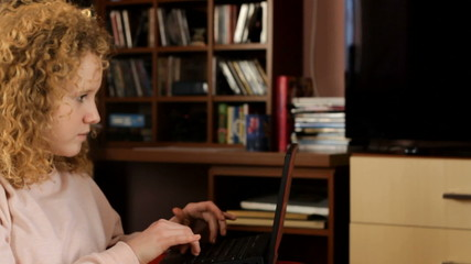 pretty student working with laptop in home - tracking shot