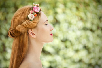 Beautiful young woman with flowers wreath in hair on natural gre