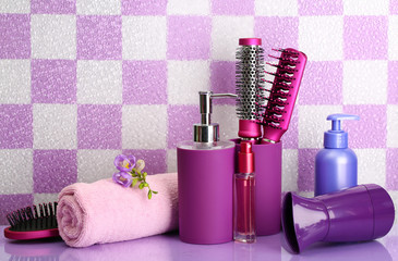 Hair brushes, hairdryer and cosmetic bottles in bathroom.