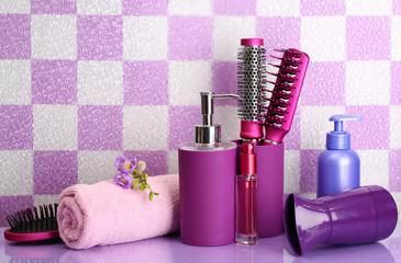 Hair brushes, hairdryer and cosmetic bottles in bathroom.