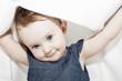 Kleinkind unter Decke grinsend