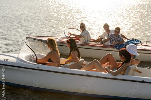 Young people driving motorboats summer lake