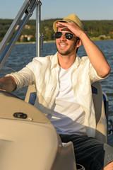 Young man navigating powerboat sunny