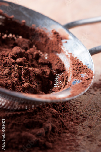 Cocoa powder on colander over wooden table