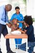 african pediatrician examining baby boy