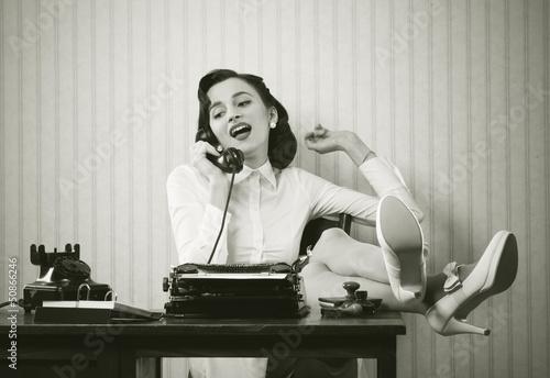 Leinwandbild Motiv Woman talking on phone at desk