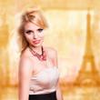 junge blonde Frau vor Paris-Hintergrund