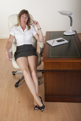 Secretary with long legs & short skirt sitting at a desk