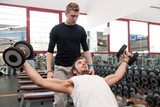 Young man and his personal trainer exercising with dumbbells
