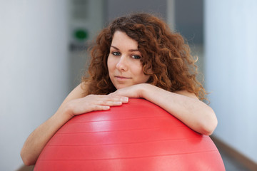 Young woman with red ball portrait in the gym.