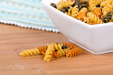Uncooked multicolored rotini pasta in white bowl