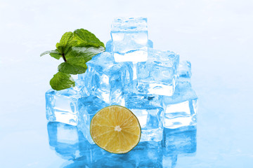 Ice cubes with mint and lime on light blue background