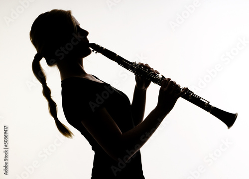 Female Musician in Silhouette Practices Woodwind Technique on Cl